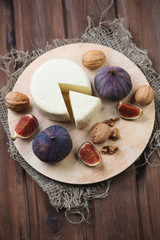 Cheese, fig fruits and walnuts, high angle view, vertical shot