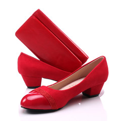 Women's shoes and a red wallet on a white background