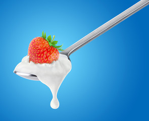 Spoon of strawberry yogurt on blue background