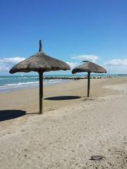Spiaggia vuota con ombrelloni di paglia