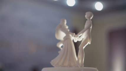 Closeup of wedding cake top bride and groom figurines