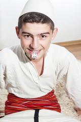 Albanischer Junge mit Kette im Mund