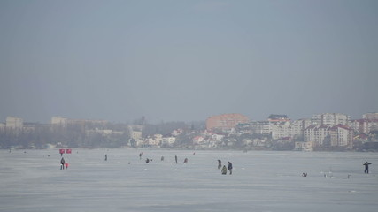 Winter lake with fishermen on a background of the city
