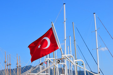 Turkish flag on the mast of a yacht on a background of blue sky