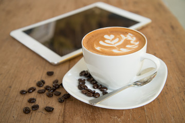 cup of coffee on table in cafe with tablet