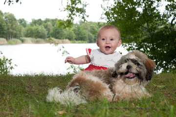 Happy baby and puppy near the lake