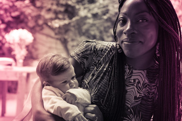 A black woman is holding a white little girl. Vintage effect