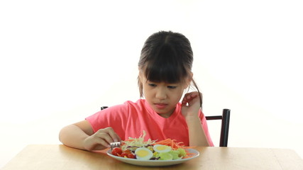 young girl doesn't like eating vegetables