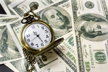 Pocket watch and dollar bills on background.