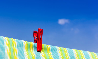 The red plastic clothespin is on the clothesline with blue sky b