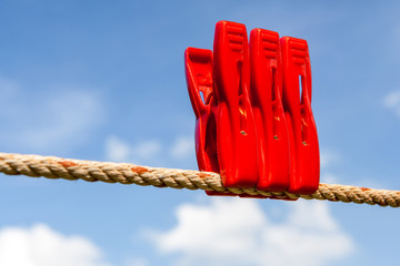 Three red plastic clothespins and a laundry line with blurry blu