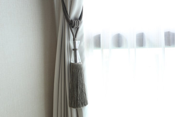 Curtain with curtain tieback at window , selective focus.