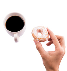 Female hand holding doughnuts with a mug of coffee