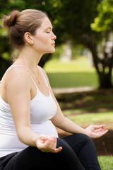 pregnant woman mother belly relaxing park yoga lotus
