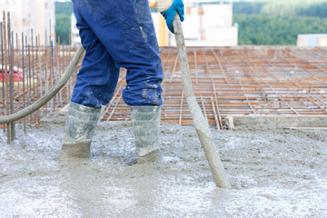 Construction worker compacting liquid cement in formwork