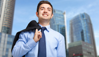 Young businessman holding the jacket over his shoulder
