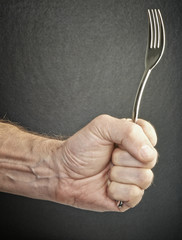 hungry and angry male hand at restaurant holding fork