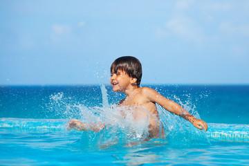 Happy boy splashing water around him in pool