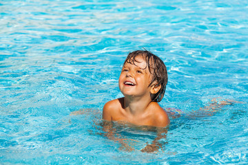 Portrait of beautiful small laughing boy in water