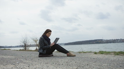 Woman use touch pad tablet pc internet technology sitting beach