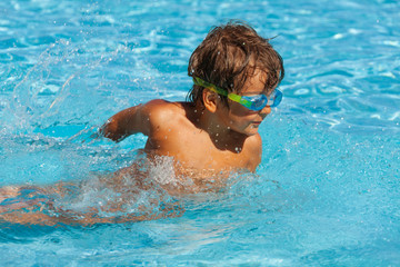 Small boy with water sport goggles swims in pool