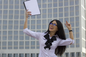 Young business woman on background of skyscraper. Joy and satisf