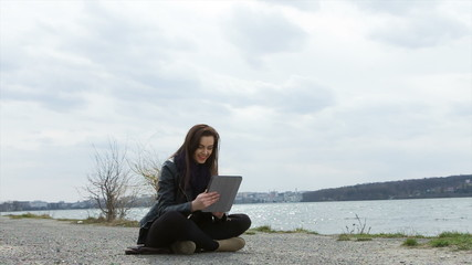 Young woman covered with blanket using tablet PC