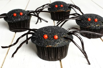 Group of Halloween spider cupcakes on white wood