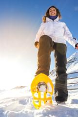 Ragazza con ciaspole su neve