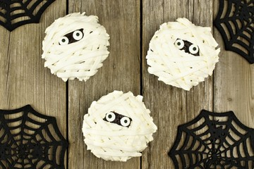 Group of Halloween mummy cupcakes on a wood background