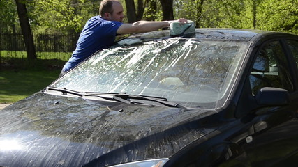 Young man carefully wash his favourite car windscreen and roof