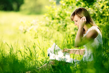 Young woman reading a book on nature