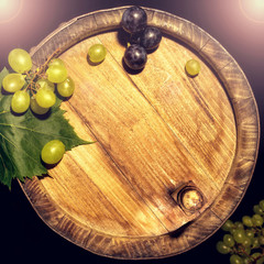Top view of the old wooden barrel, with green and black grapes