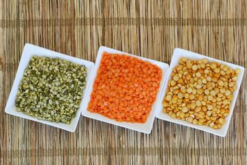 Selection of pulses in white bowls with copy space
