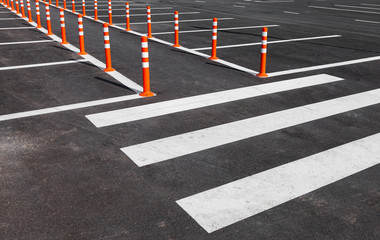 White traffic markings with a pedestrian crossing on a gray asph