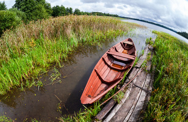 Old wooden boat at the lake in summer day
