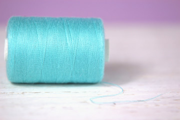 Turquoise, thread on white wooden and lilac background