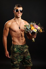 Young soldier holds bouquet with beauty autumn decoration