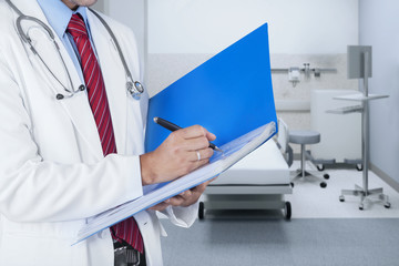 Doctor writing report on a folder