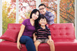 Family sitting on sofa and smiling at camera