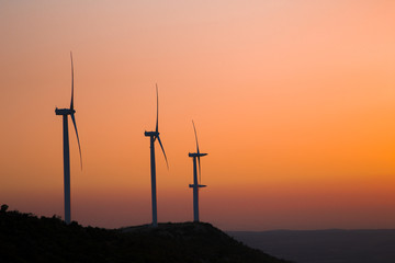 Wind turbines silhouette on the mountain during sunset