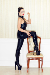 Woman step on chair in latex boots