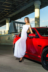 Elegant young woman posing near the red car