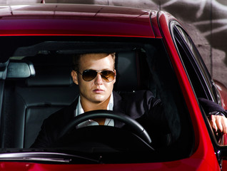 Yound elegant guy driving modern car