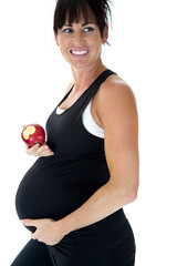 pregnant model holding her belly and holding an apple