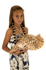 adorable tan girl holding seashell wearing an island style dress