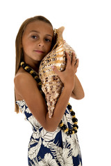 cute girl wearing a tropical dress holding a large seashell