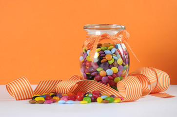 Halloween trick or treat candy on orange background