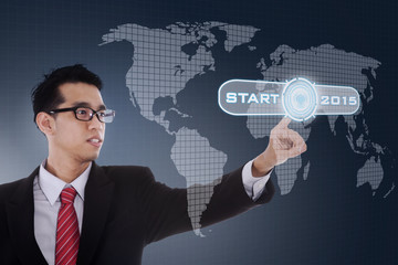 Young business person with start button