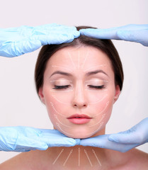 Face massage. Hands in rubber gloves touching face of young